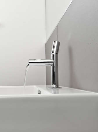 detail of washbasin and steel faucet in a modern bathroom Stock Photo