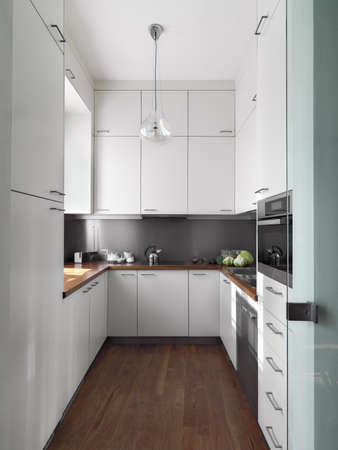 cardunculus scolymus: detail little white modern kitchen of wood floor and wood worktop