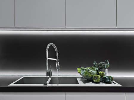 llave de agua: verduras en la mesa de trabajo en una cocina moderna Foto de archivo