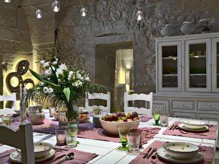 Esstisch mit Vase von weißen Blüten und Schüssel Feigenkaktus in einem Speisesaal mit Steinmauern