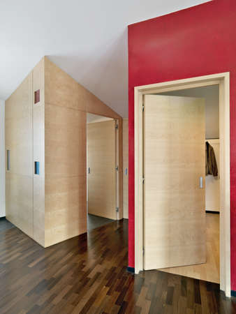 wood floor: detail of modern corridor in the attic room with wood floor  and red wall