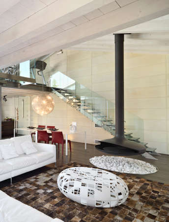 modern living room in the attic with white leather sofa and black iron fireplace photo