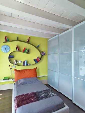 Jungen moderne Schlafzimmer mit Glasschrank und Bücherschrank und Holzdecke