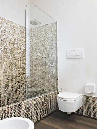 mosaic tile: dettaglio di lavabo e vaso sospeso con box doccia in muratura e piastrelle di mosaico a parete