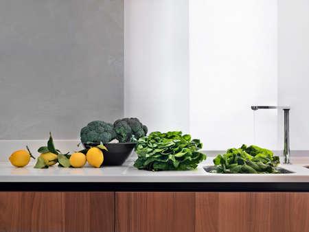 Gemüse auf Arbeitsplatte in der Nähe von hte dem Waschbecken in der modernen Küche Lizenzfreie Bilder