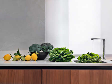 lactuca: vegetables on hte worktop near to the sink in the modern kitchen