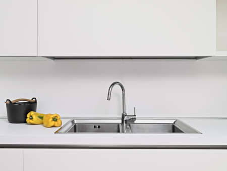 two yellow peppers next to the nonstick saucepan near to the steel sink in a modern kitchen in white laminate photo