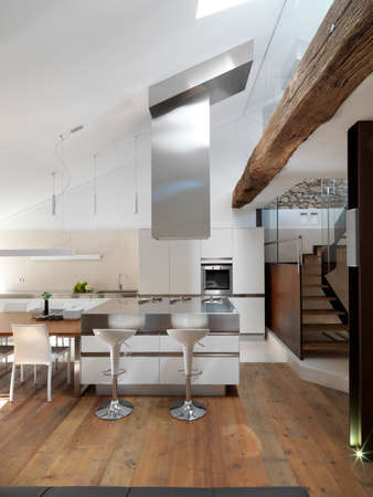 penthouse: view of island modern kitchen with wood floor near to staircase in the penthouse