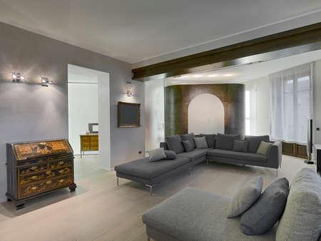 antiken Möbeln und grauem Stoff Sofa im modernen Wohnraum mit Holzboden