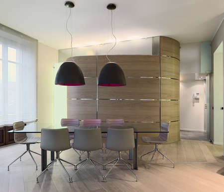 glass dining table in a modern apartment with boiserie and wood floor