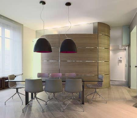 pisos de madera: mesa de comedor de vidrio en un moderno apartamento con boiserie y piso de madera Foto de archivo