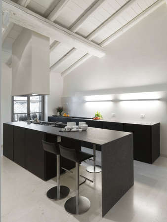 modern island kitchen with wood ceiling and marble floor in the penthouse Stock Photo