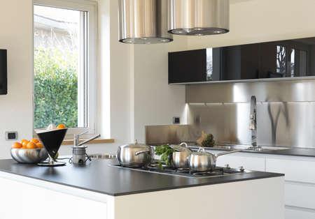moderne Küche mit Stahlpfannen und Gemüse auf dem Stahl oben