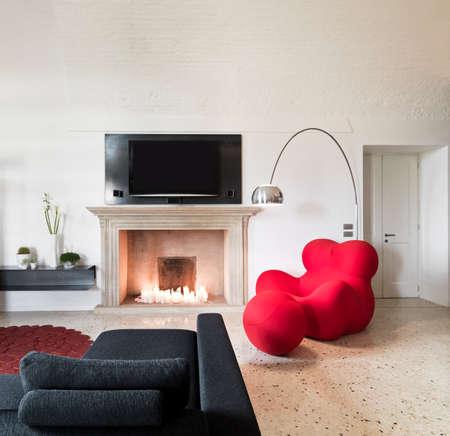 schwarzen Sofa, rote Sessel und Kamin in einem modernen Wohnzimmer mit Fernseher