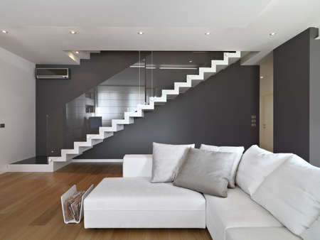 wood floor: fabric sofa in the modern living room with staircase and wood floor Stock Photo