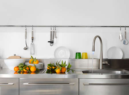 kitchen sink: fresh orange on the worktop near to sink in a modern kitchen