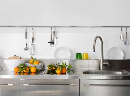 frische Orange auf der Arbeitsplatte in der Nähe, in einer modernen Küchenspüle
