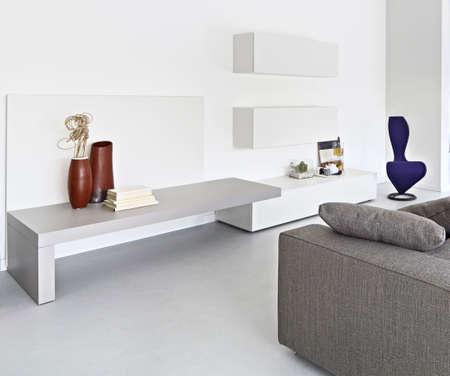 vista interno di un moderno salotto con divano in tessuto e pavimento in cemento