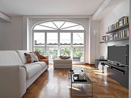 Innenansicht eines modernen Lving Raum mit Stoff Sofa und Bücherregal mit Blick auf die Terrasse