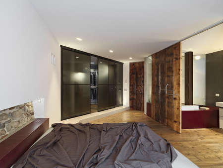 interior view of a modern bedroom overlooking on the bathroom with wood floor and wardrobe  Progetto arch. Giorgio Parise, Marostica VI