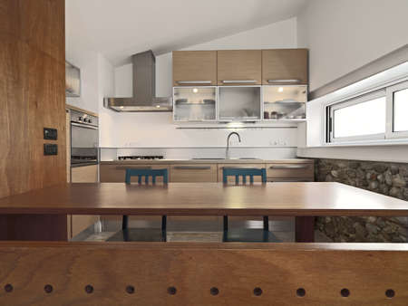interior view of a wood modern kitchen with island and wall cabinets