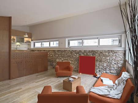 vista degli interni di soggiorno con divano vintage arancio e poltrona con vista sulla cucina hte, il pavimento è di marmo