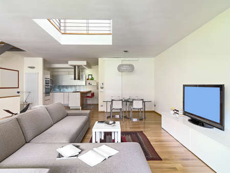 interior view of a modern living room in the attic room with wood floor overlooking on kitchen and dining table