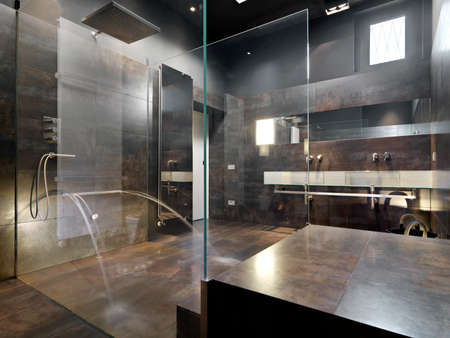shower cubicle: view a large masonry shower cubilce and masonry bathtub  with glass partition and dark tiled overlooking on the washbasin Editorial