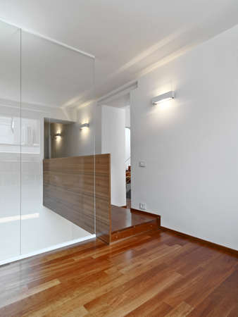 glass partition: interior view of apartment overlooking on the landing with wood floor and glass banister Stock Photo