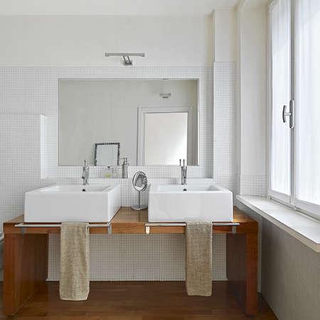vista interna del bagno moderno con due lavabo e pavimento in legno