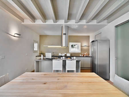 interior view of a modern kitchen with wood ceiling and kitchen island