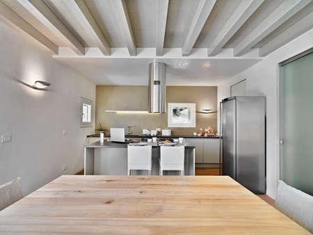 vista interna di una cucina moderna con soffitto in legno e cucina isola