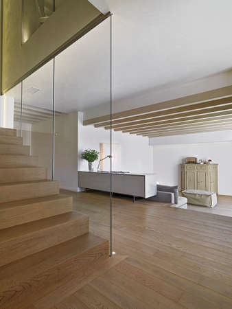 inerior view of a modern apartment with in foreground the wood staircase overlooking on the living room