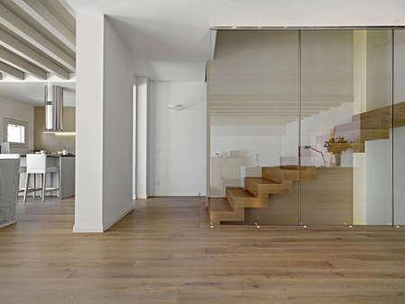 auf der Holztreppe in einem modernen Wohnzimmer mit Blick auf den Küchen Vordergrund