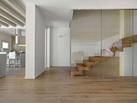 foreground on the wood staircase in a modern living room overlooking on the kitchen Foto de archivo