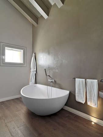 interiors: detail of a modern bathtub in a bathroom in the attic room Stock Photo