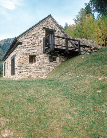 meadowland: exterior view of a stone houe mountain, Itlay