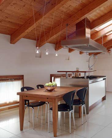 vista interno di una cucina modenr in mansarda con soffitto in legno e tavolo da pranzo