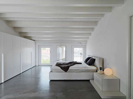 modern bedroom in the attic room with resin floor and wooden ceiling Archivio Fotografico