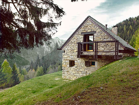 meadowland: exterior view of a stone house in the mountain Stock Photo