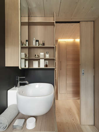 sliding door: close up of washbasin in a modern bathroom with wood  sliding door and wood paneling
