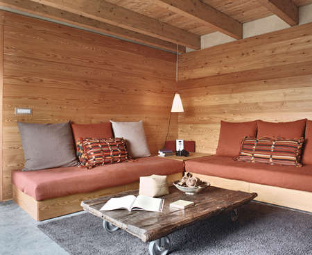 interior view of rustic living room with wood paneling and stone floor