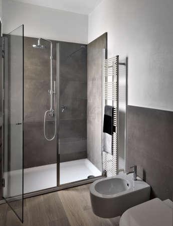 interieur bekijken van de moderne bahtroom met glazen douchecabine en houten vloer Stockfoto