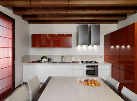 wood ceiling: interior view of a modern kitchen with red furniture and wood ceiling