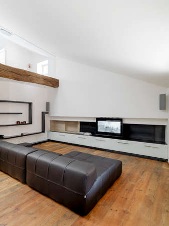 brown leather sofa: interior view of modern living room in attic room with brown leather sofa and television and  wood floor