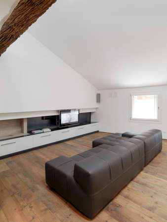 attic room: brown leather sofa in the attic room with television and wood floor for modern living room