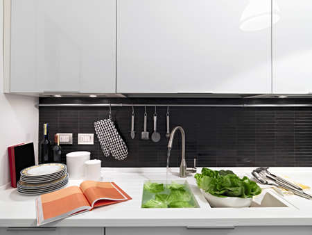 kitchen cabinet: objects and vegetables on the worktop in the modern kitchen near to sink