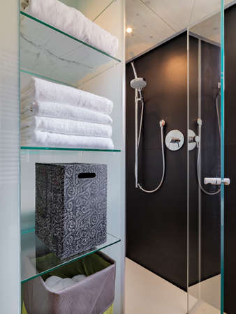 shower cubicle: white towel and box on the glass shelves overlooking on glass shower cubicle in the modern bathroom Stock Photo