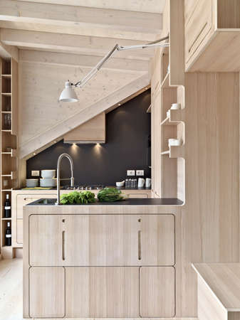 kitchen island: foreground oh a wooden modern kitchen island in the attic room