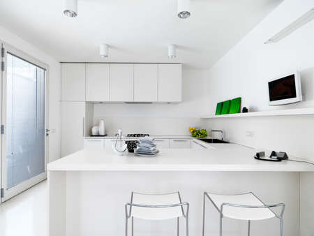 kitchen cabinet: interior view of a white modern kitchen with vegetables on the wotktop